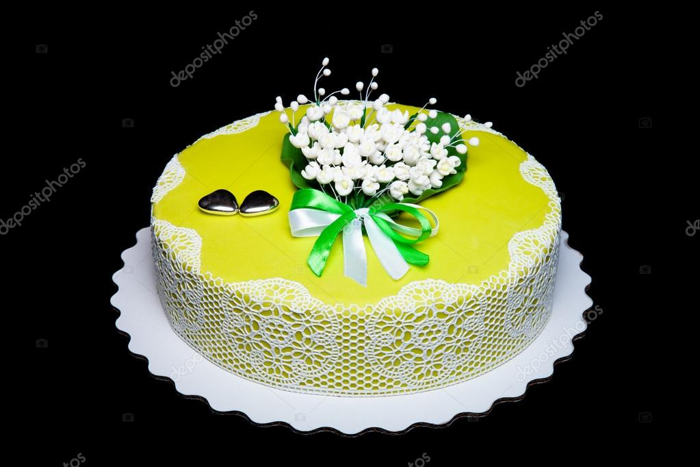 Wedding cake with lace and flowers on green background. Toned ...