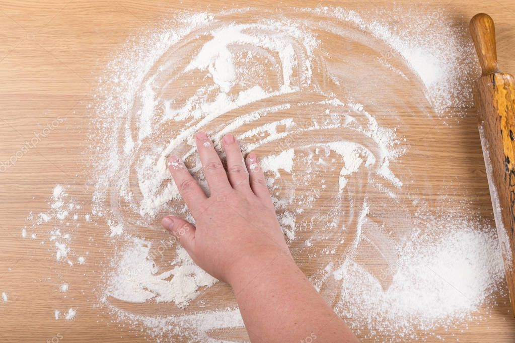 Plump women's hands work with dough on a light wooden table