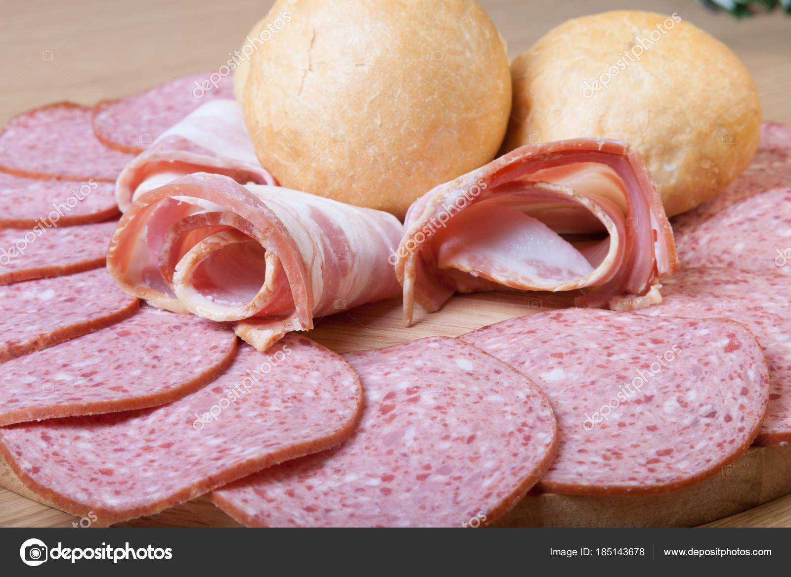 Salchicha y pan sobre una mesa de madera ligera. Profundidad de fiel ...
