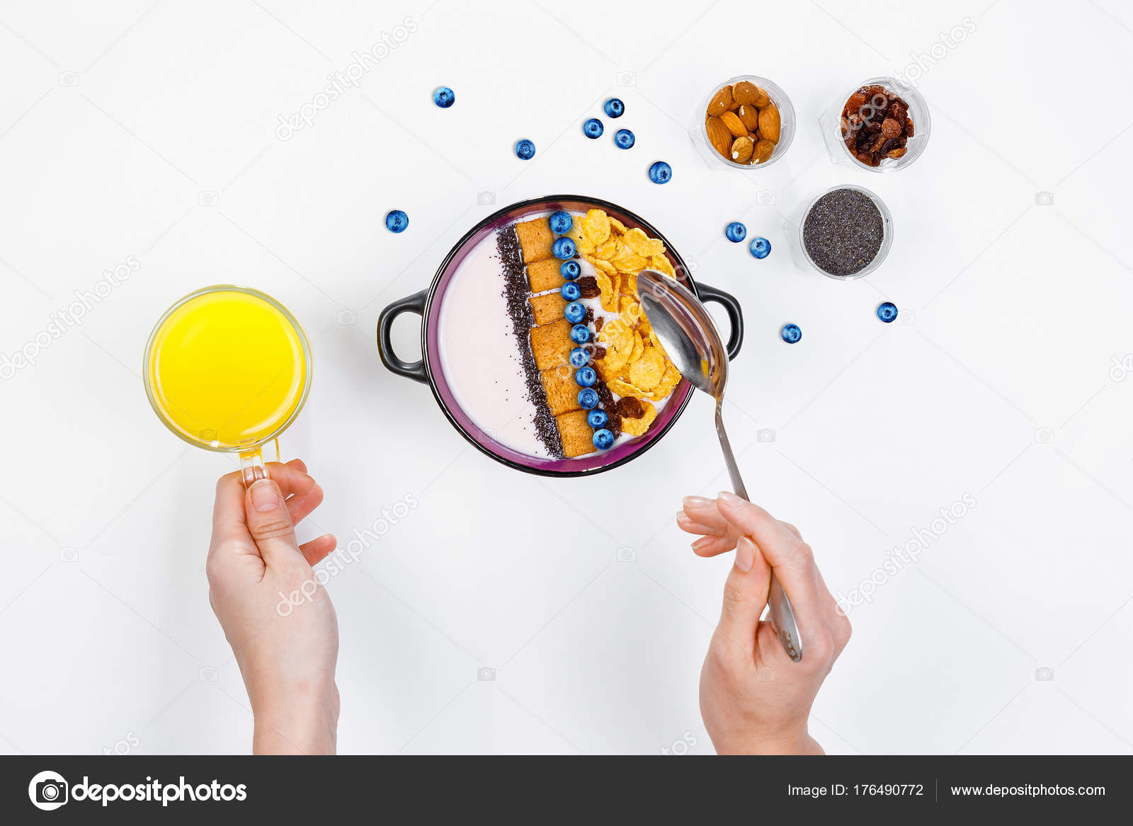 ... a spoon over a bowl with homemade yogurt and cornflakes, and fresh  blueberries, a glass of orange juice on a white background, top view, flat  lay.