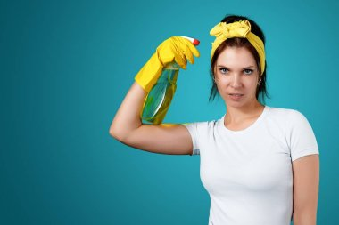 The girl, the cleaning lady after cleaning, stands with a displeased face, holding a cleanser in her hands on a blue background. The concept of cleanliness in the house, cleaning the premises