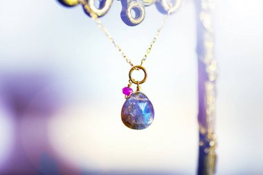 golden necklace with with big labradorite with small ruby on black background.