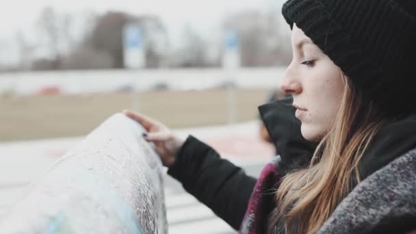 Beautiful young woman looking in the tourist map to find right street. Tourist girl looking aroung the street with map