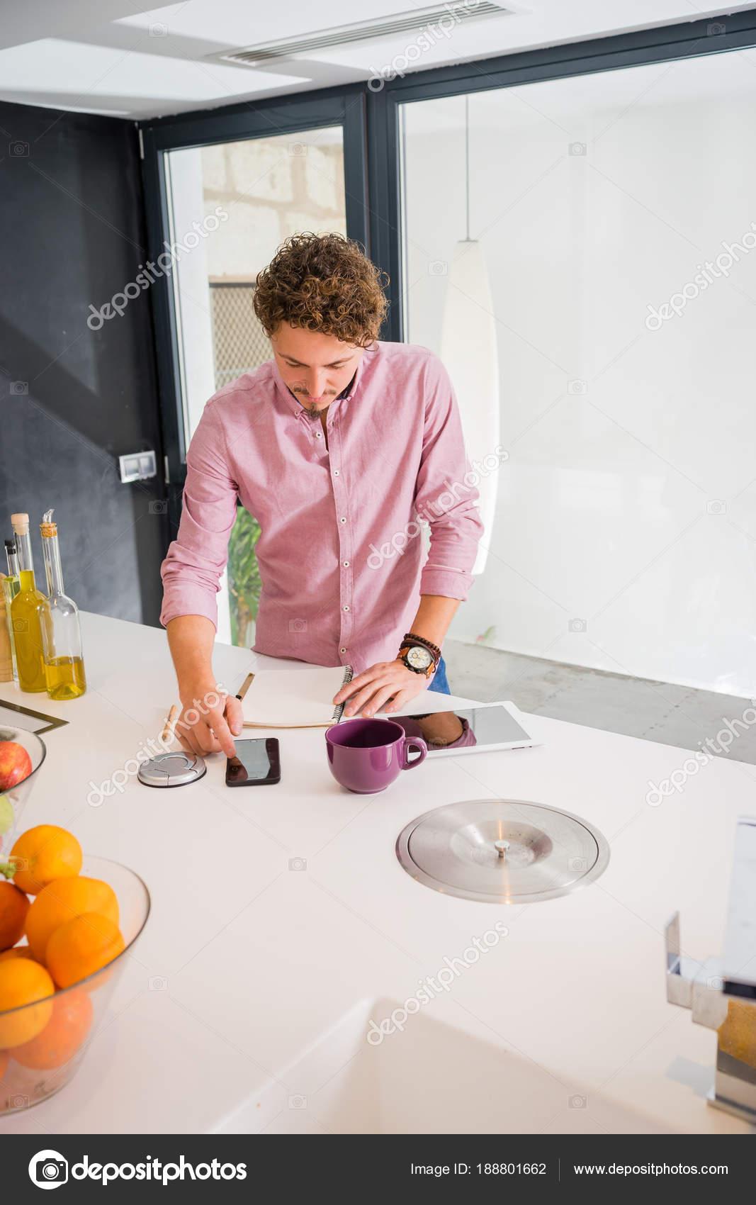 Hombre sonriente, de pie en la cocina, cálculo en su teléfono ...