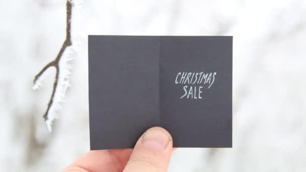 karácsonyi eladó kreatív ötletre, kezében egy kártya