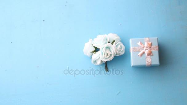 Rózsa és ajándék doboz kék háttérrel