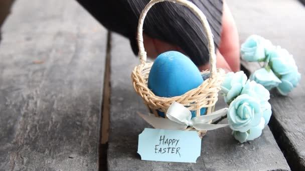Veselé velikonoce. Modré vajíčko na rustikální stůl a košík s značky