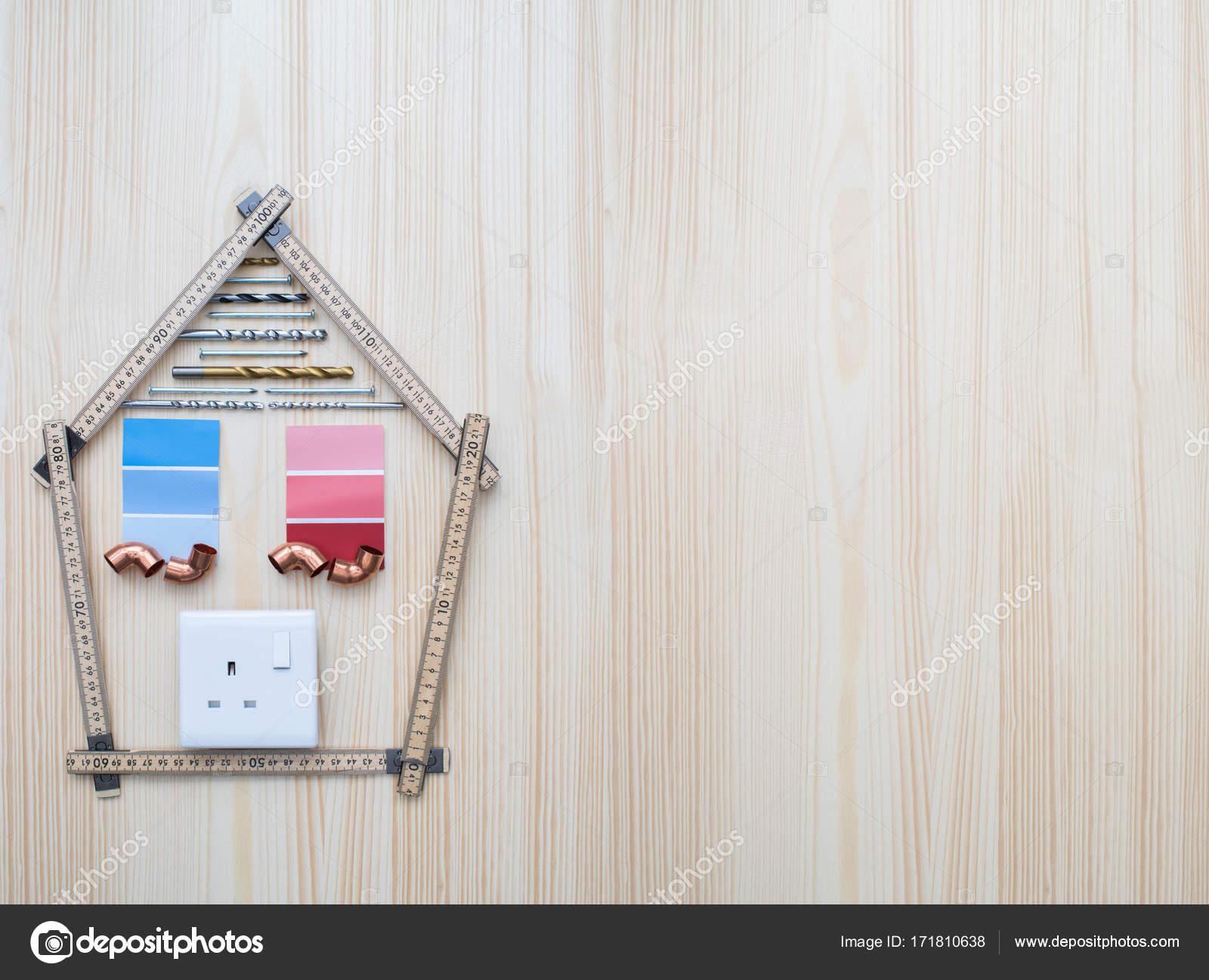 Bauteile, die In Form von Haus auf hölzernen Hinterg angeordnet ...