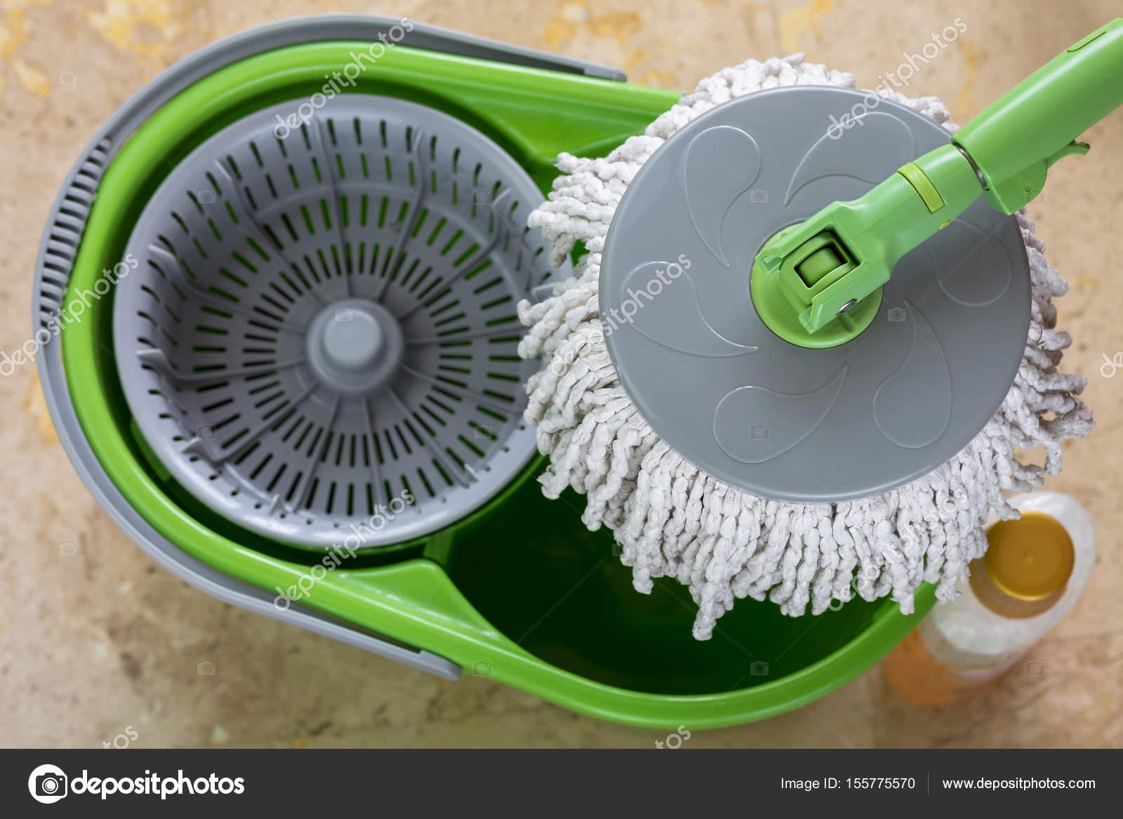 f5565853c Usa spin mop con cabezal de microfibra, mango verde en un cubo para limpiar  —
