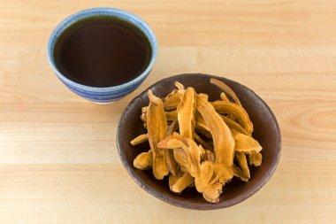 Bowl of herbal sliced dried Lingzhi mushroom next to hot Reishi tea