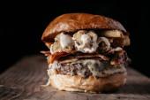 Fotografie saftige Burger auf dunklem Hintergrund mit negativem Leerzeichen