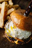 Frühstücksburger mit Spiegelei auf dunkler, rustikaler Oberfläche
