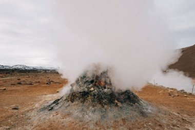 Fumarole evacuating pressurized hot sulfurous gases from volcanic activity in the geothermal area of Hverir Iceland near Lake Myvatn