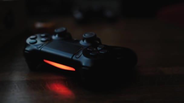 Videojáték vezérlő egy fa asztalon egy sötét szobában piros háttérvilágítással