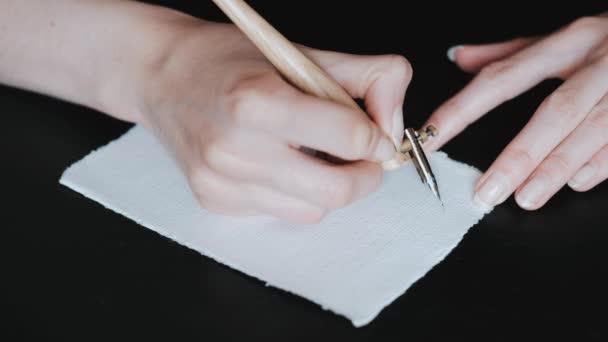 Mädchenhände, die Buchstaben in kursiver Schrift in Kalligraphie darstellen