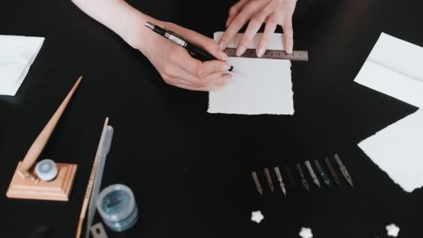 Mädchen zeichnet gerade Linien auf ein weißes Laken. Kalligraphie, Nahaufnahme von oben