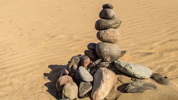 Rock zen pyramid of colorful stones. Concept of balance, harmony and meditation, built on sea sand