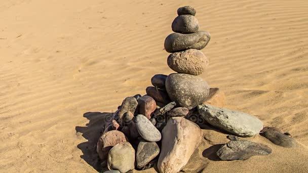 Rock zen pyramida barevné kameny. Koncept rovnováhy, harmonie a meditace, postavený na mořském písku