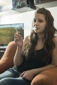 Lány füst cigaretta a szobában