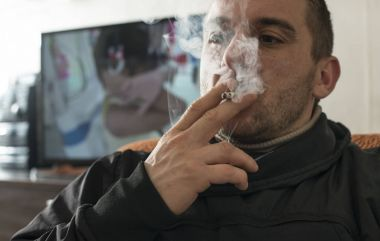 Man smokes a cigarette in the house.