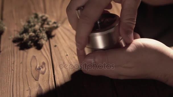 Schleifen Zapfen von Marihuana mit einer Schleifmaschine Nahaufnahme. Unkraut, Knospen und Schleifer in Zeitlupe details