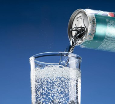 Mineral sparkling water pours from an aluminum can into a glass