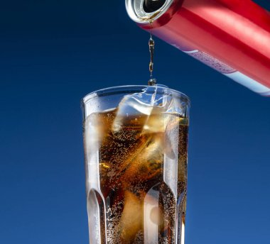 Carbonated drink pours from an aluminum can into a glass