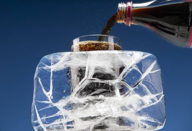 A large piece of ice covered with cracks in the background of a glass of carbonated drink