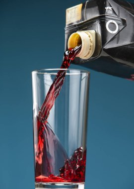 Cherry juice is poured from the packaging into a glass