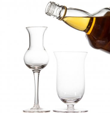 Two empty glasses in the shape of a tulip. A bottle of whiskey.