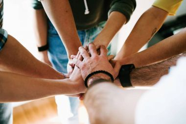 Group of people joining hands together. College students teamwork stacking hands. Partnership. Team work.