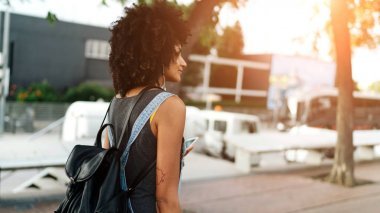 View from the back photo of young woman with afro hairstyle wearing casual clothes and holding a smartphone.Hipster girl with a backpack listening to the music on a mobile phone.Flare light