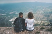 Photo Hikers with backpacks enjoying valley view from top of a mountain