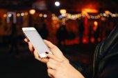 Oříznout obrázek ženských rukou pomocí smartphone s prázdnou kopii prostor obrazovky na pozadí bokeh