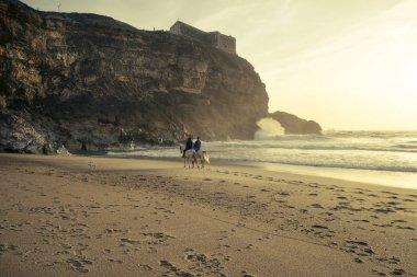couple has a romantic stroll on horsebacks along the ocean beach. romantic walk on horsebacks at sunset