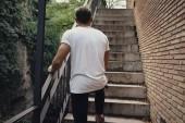 Man wearing blank t-shirt walking on stairs