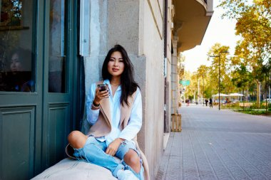 young Asian woman sitting in modern coffee shop and using smartphone