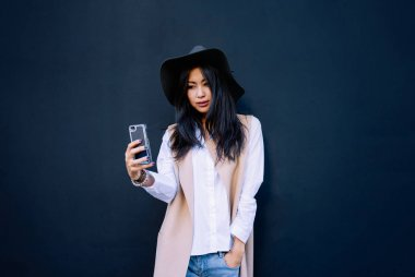 Asian young beautiful woman using smartphone and talking selfie on a black wall background