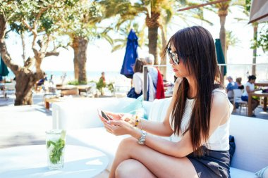 Young woman is holding smartphone while sitting in a lounge cafe on a sunny day
