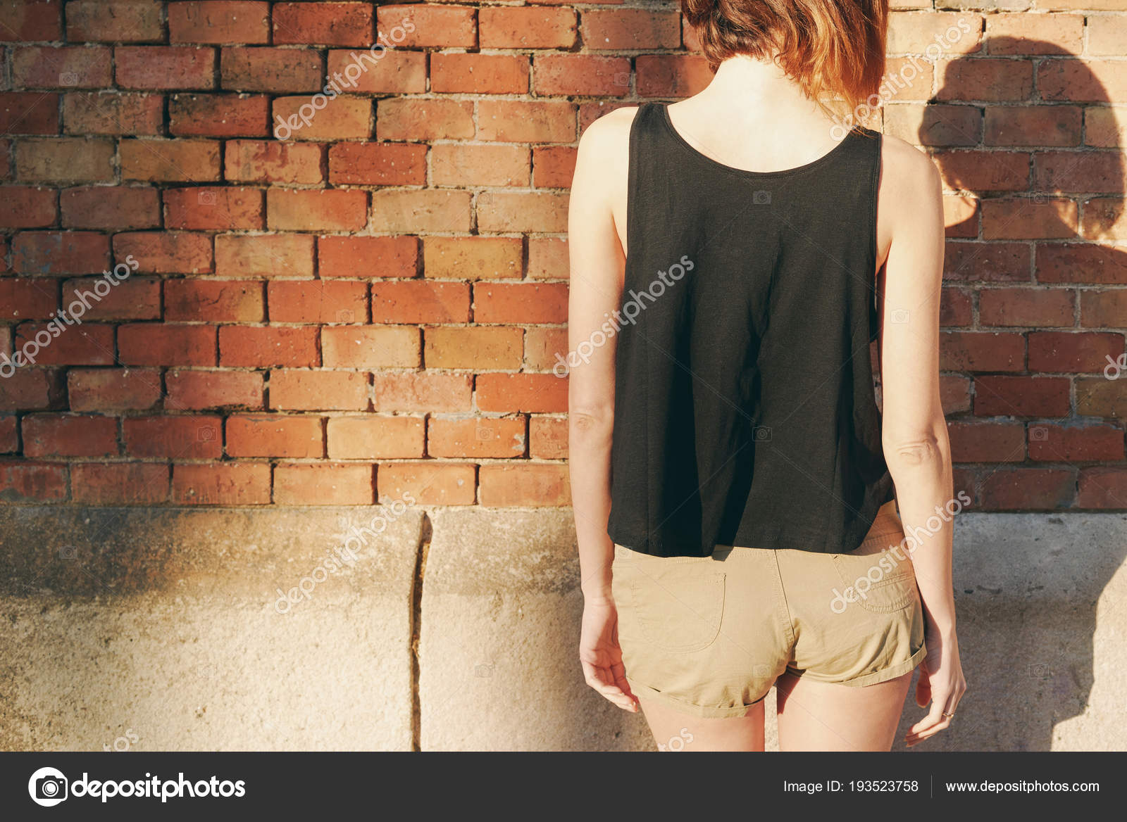 8f49c84211770 Young woman wearing in a black blank T-shirt without sleeves posing against  a background of a brick wall — Photo by ...