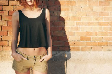 young woman wearing in a black blank T-shirt without sleeves posing against a background of a brick wall