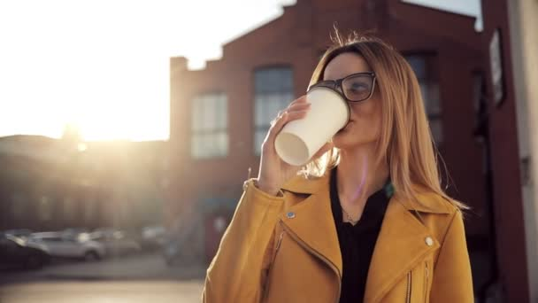 A girl drinks coffee and walks around the city