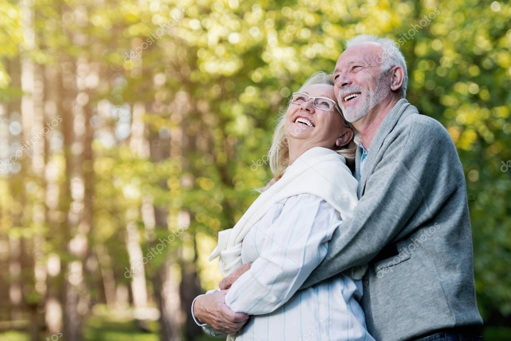 Happy senior couple hugging   outdoors in nature