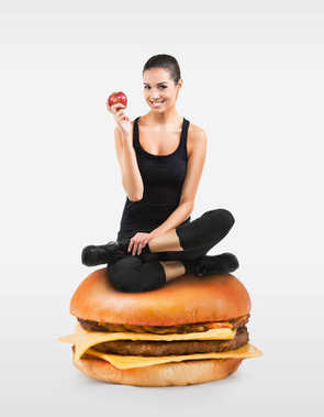 Beautiful fit girl sitting on a hamburger holding an apple