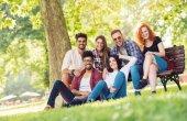Skupina mladých lidí, které baví venku na lavičce v parku