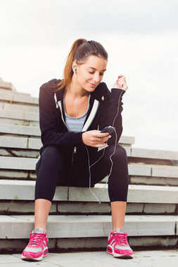 Young woman taking a break from exercising outside with cellphone