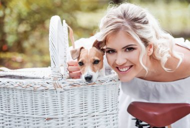 Beautiful blonde woman outdoors in a park with a pet dog in a bicycle basket