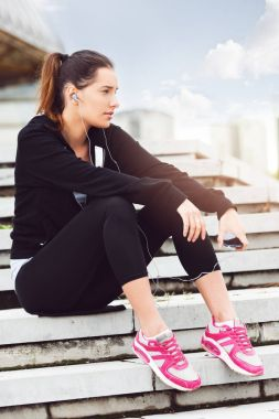 Young woman taking a break from exercising outside