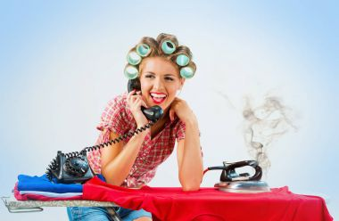Housewife talking on the phone while ironing on blue background