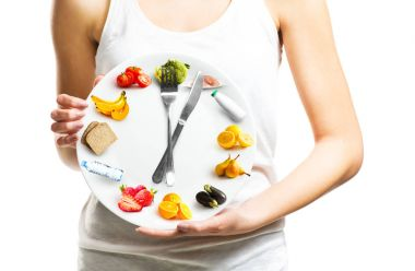 Beautiful young woman holding a plate with food, diet and time concept